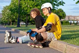 image of inline skating  - young heterosexual couple put on inline skates - JPG