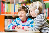 Children in a library listening to audio books with headphones poster