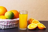 Fresh Orange Juice In Glass Beaker And Whole Oranges In Basket On A Table. Sliced Orange Slices And  poster