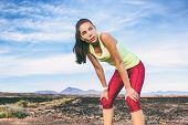 Tired runner girl taking a break breathing during jogging training workout outdoor on desert trail.  poster