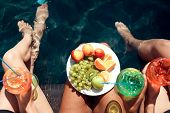 Top View. Girls In Swimsuits Eat Fruits And Drink Cocktails In Swimming Pool In Summertime. Summer V poster