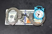 Handcuffs, Money And Alarm Clock On Dark Background, Bail Concept poster
