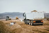 Industrial Dumper Trucks Working On Highway Construction Site, Loading And Unloading Earth. Heavy Du poster