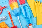 Group Of Objects For House Cleaning. Duster Broom And Spray For Cleaning On Blue Wooden Background.  poster
