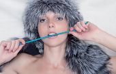 Young woman in fur hat  on light background