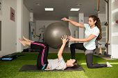 Physical Therapist Assisting Young Caucasian Woman With Exercise With Yoga Ball During Rehabilitatio poster