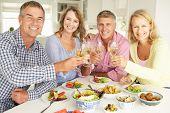 Meados de casais de idade desfrutando de refeição em casa