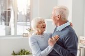 Loving Couple. Joyful Elderly Husband And Wife Dancing In The Living Room While Smiling At Each Othe poster