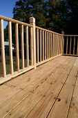 stock photo of 2x4  - A wooden deck and rail in sunlight. Perfect for construction advertising.