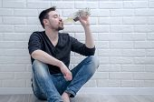 Depressed young man drinking wine alone. Depressive guy drinks alcohol poster