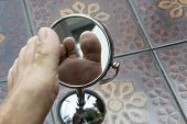 Person Looking At The Sole Of The Foot In A Mirror, To Check If There Is No Diabetic Foot, As Possib poster