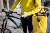 Man Delivering Food With Thermo Bag And Bicycle, Checking An Order With Smart Phone, Close-up View poster
