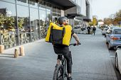 Young Bearded Courier Delivering Food With A Yellow Thermal Backpack, Riding A Bicycle In The City.  poster