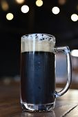 Glass Of Beer On Wooden Table. Beer In A Glass. Beer In A Glass At A Pub. Dark Beer With Foam In A C poster