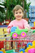 Child In Shoppingcart With Toy Car