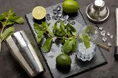 Set of bar tools: cocktail shaker, muddler and glass with ice, lime and mint  on dark stone  table.  poster