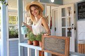 Young Woman With Watering Can And Home Plants On Veranda, Space For Text poster