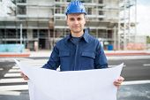 Smiling site manager reading a blueprint in front of a construction site poster