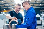 Skillful master discussing a workpiece with his apprentice or trainee poster