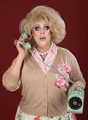 stock photo of drag-queen  - Surprised drag queen holding telephone over maroon background - JPG