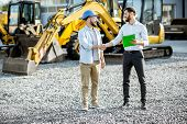 Builder Choosing Heavy Machinery For Construction With A Sales Consultant Shaking Hands On The Open  poster