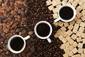 three cups of coffee on mixed coffee and sugar background