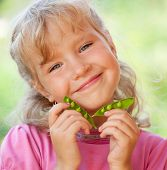 stock photo of healthy eating girl  - Child eating pea pod outdoors - JPG