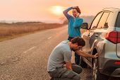 Couple Repairing Car Flat Tire On The Road In Autumn Sunset And Calling For Roadside Assistance, Sel poster
