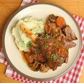 Lamb shank braised with vegetables and served with mashed potato.
