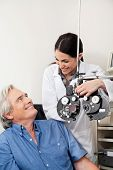 Caring eye specialist smiling at mature patient before performing eye test with phoropter