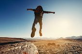 Hiker With Backpack Jumps From Big Rock Against Mountains And Sunset poster