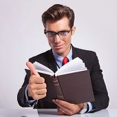 attractive young business man sitting at the desk with a book in his hand and showing thumbs up sign