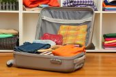 picture of carry-on luggage  - Open grey suitcase with clothing in room - JPG