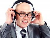 Businessman wearing earphone struggling to hear.