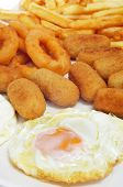 closeup of a spanish combo platter with fried eggs, croquettes, calamares and french fries
