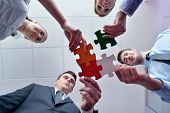 stock photo of jigsaw  - Group of business people assembling jigsaw puzzle and represent team support and help concept - JPG