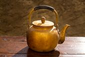 Antique brass teapot on vintage wooden aged table