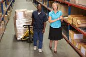 Businesswoman And Male Worker In Distribution Warehouse