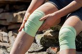 Athlet olhando a menina corrige atadura em joelhos ao ar livre