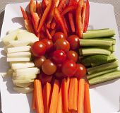 stock photo of crudites  - Closeup of assorted fresh raw vegetables on a white platter - JPG