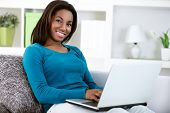 stock photo of web surfing  - young black girl with laptop computer - JPG