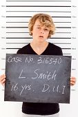 stock photo of mug shot  - teen boy get arrested for drunk driving and taking police mug shot - JPG