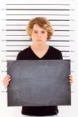 teenage boy holding a blackboard taking criminal mug shot