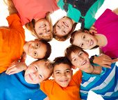 picture of brunete  - Circle of smiling positive kids looking down  - JPG