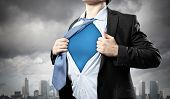 image of superman  - Image of young businessman showing superhero suit underneath his shirt standing against city background - JPG