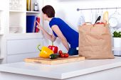 Unpacked Groceries And A Woman At The Cookbooks