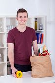 Happy Young Man Unpacking Groceries In The Kitchen