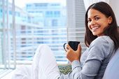 stock photo of flavor  - Woman enjoys fresh coffee relaxing at home on the sofa couch - JPG