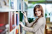 young college student in a library selecting books from bookshelf during self education