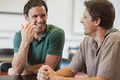 stock photo of maturity  - Two friendly male mature students chatting while sitting in class room - JPG